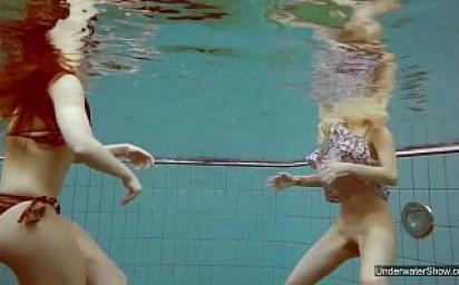 Two hot chicks enjoy swimming pool naked